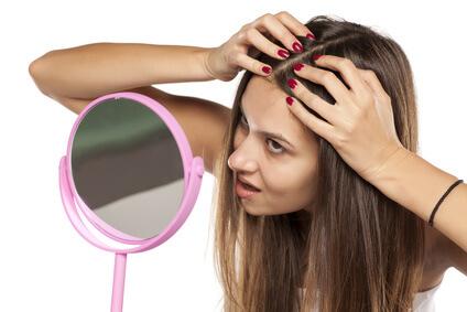 鏡で頭皮を見る女性
