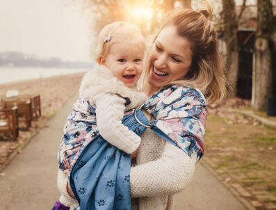 抱っこ紐で赤ちゃんを抱っこする母親