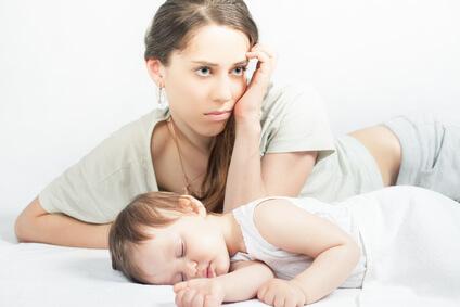 寝ている子供と疲れた母親
