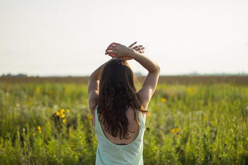 草原に立つ後ろ姿の女性