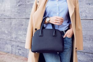 Trendy woman in beige coat with black big bag