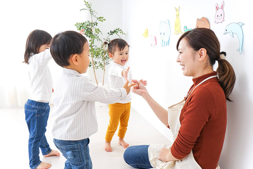 nursery-school-teacher-playing-kids